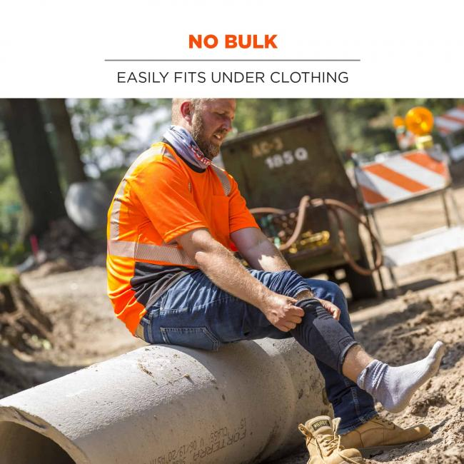 No bulk: easily fits under clothing. Image shows construction worker putting on under clothing.